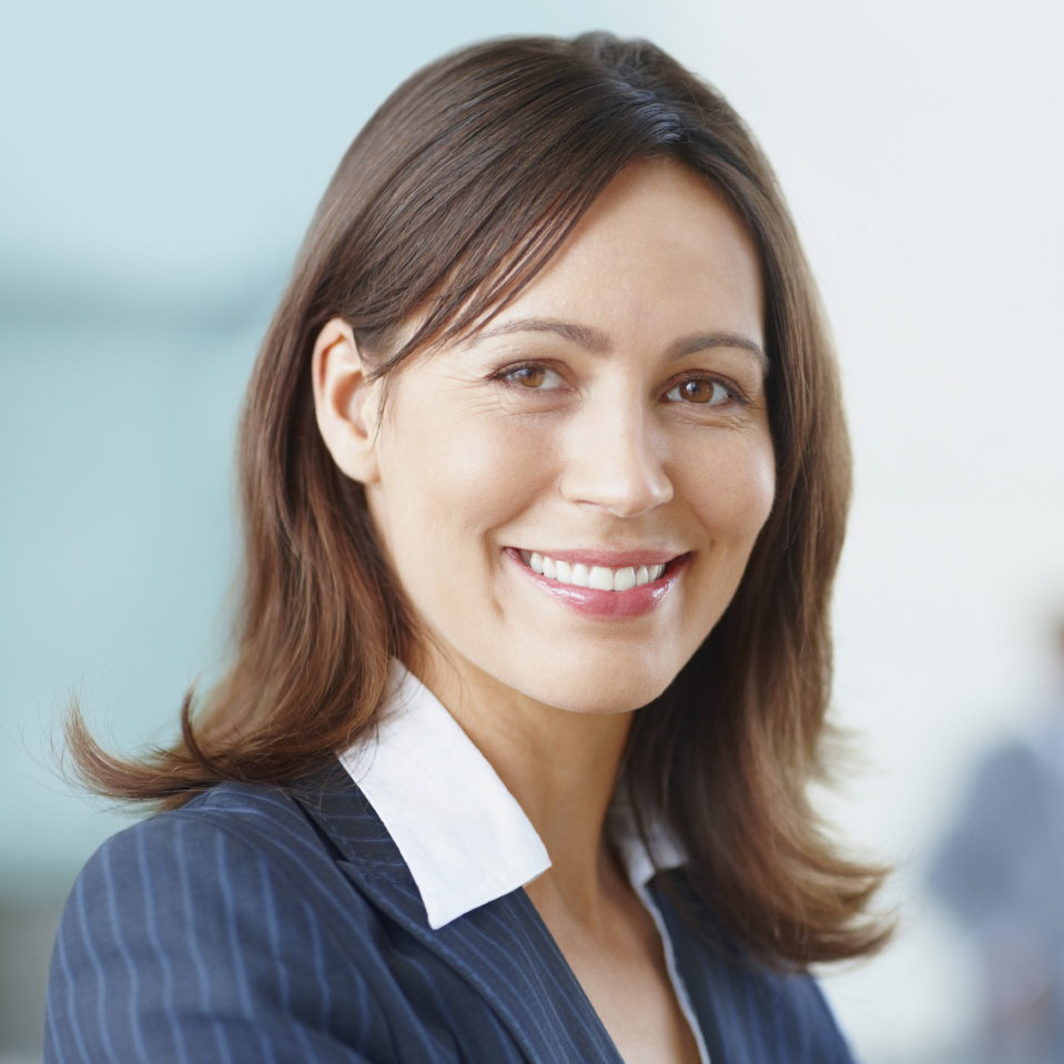 A woman in a blue pinstriped blazer from the chest up. She is smiling at the camera.